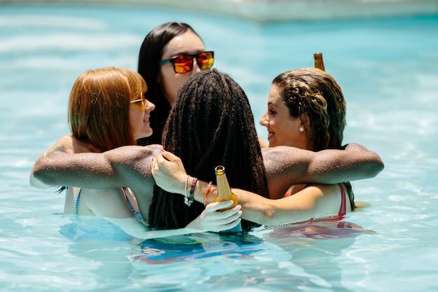 Gruppo di giovani di diverse etnie in una piscina che abbraccia in un cerchio con birre Foto Premium
