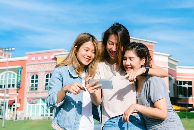 Gruppo di giovani donne asiatiche si selfie con un telefono in una città pastello dopo lo shopping Foto Gratuite