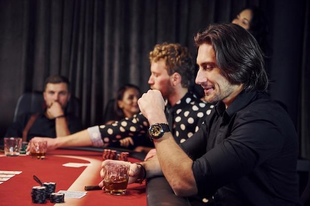 Gruppo di giovani eleganti che giocano a poker nel casinò insieme Foto Premium