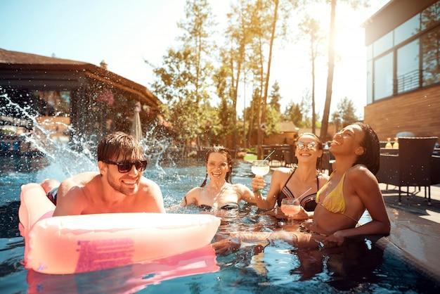 Gruppo di giovani felici che nuotano in piscina Foto Premium