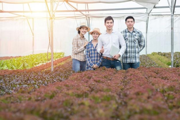 Gruppo di giovani imprenditori asiatici agricoltore uomo e donna in serra azienda agricola biologica idroponica, Foto Premium