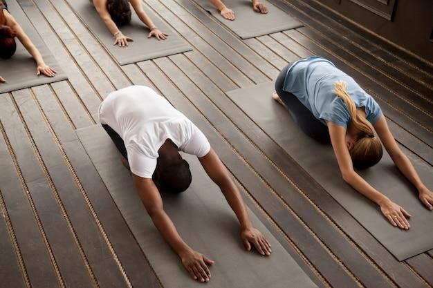 Gruppo di giovani in posa balasana, vista dall'alto Foto Gratuite