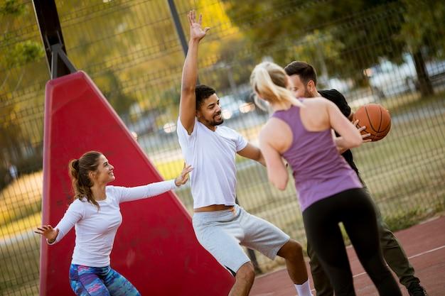Gruppo di giovani multirazziali che giocano a basket all'aperto Foto Premium