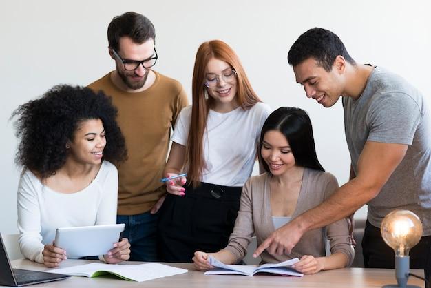 Gruppo di giovani positivi che lavorano insieme Foto Gratuite