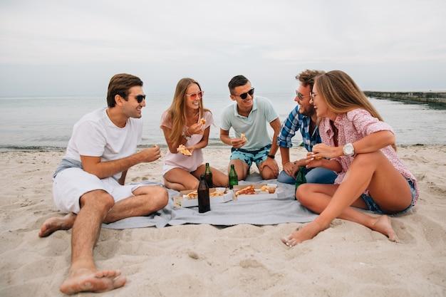 Gruppo di giovani ragazzi e ragazze sorridenti che riposano insieme sulla spiaggia, seduti vicino al mare Foto Gratuite