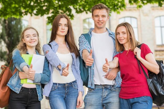 Gruppo di giovani studenti di fronte all'edificio scolastico Foto Gratuite