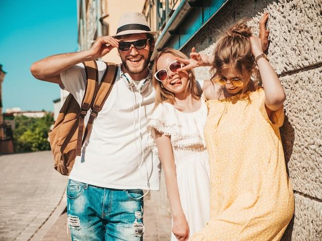 Gruppo di giovani tre amici alla moda che posano nella via. moda uomo e due ragazze carine vestite in abiti estivi casual. modelli sorridenti divertendosi in occhiali da sole. donne allegre e tipo all'aperto Foto Gratuite