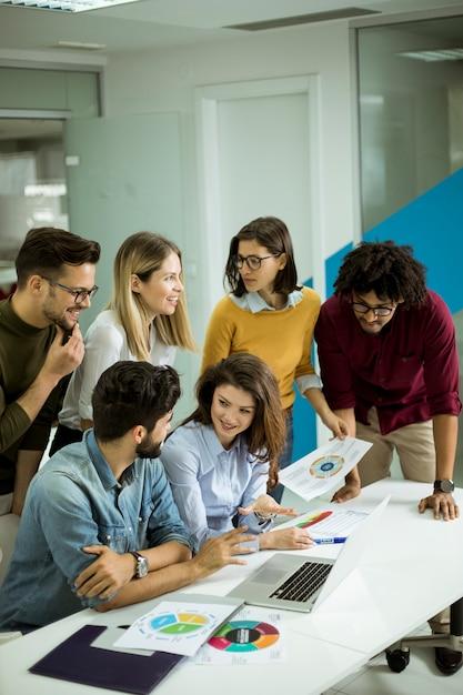 Gruppo di giovani uomini d'affari multietnica lavorando e comunicando insieme in ufficio creativo Foto Premium
