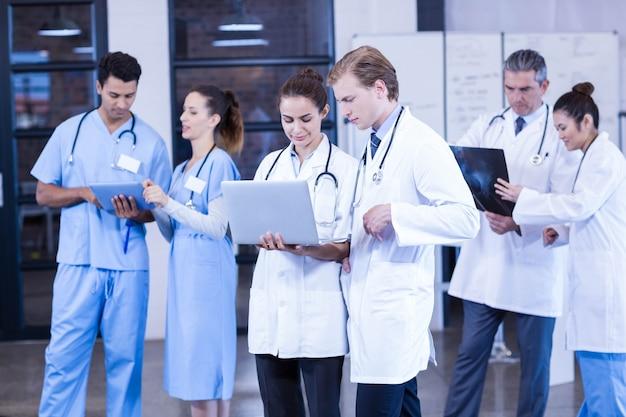 Gruppo di medici che discute rapporto dei raggi x e che utilizza computer portatile e compressa digitale nell'ospedale Foto Premium