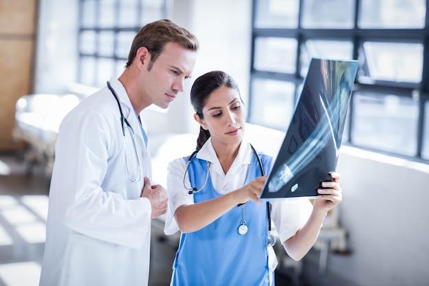 Gruppo di medici che esamina insieme raggi x all'ospedale Foto Premium