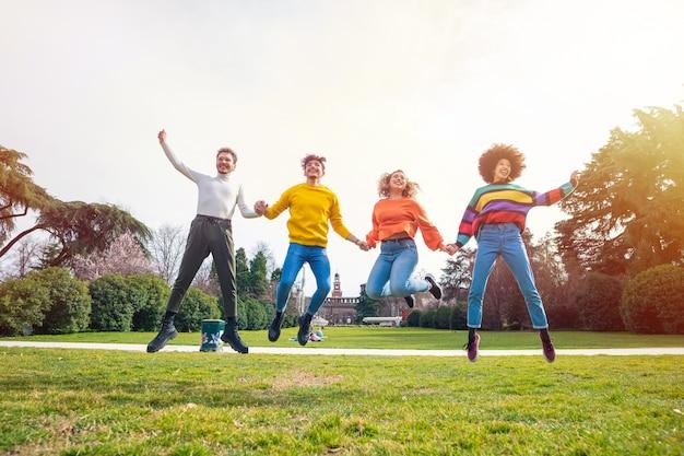 Gruppo di persone amici saltando la retroilluminazione esterna Foto Premium