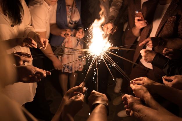 Gruppo di persone che accendono insieme le luci del bengala. solidarieta. Foto Premium