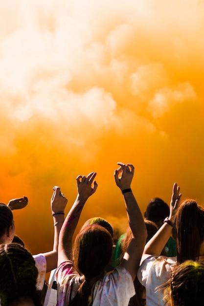 Gruppo di persone che ballano di fronte a un'esplosione di polvere di holi Foto Gratuite