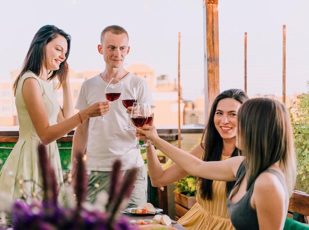 Gruppo di persone che tostano alla festa sul tetto Foto Gratuite