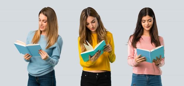 Gruppo di persone con abiti colorati in possesso di un libro e godendo la lettura sul retro colorato Foto Premium