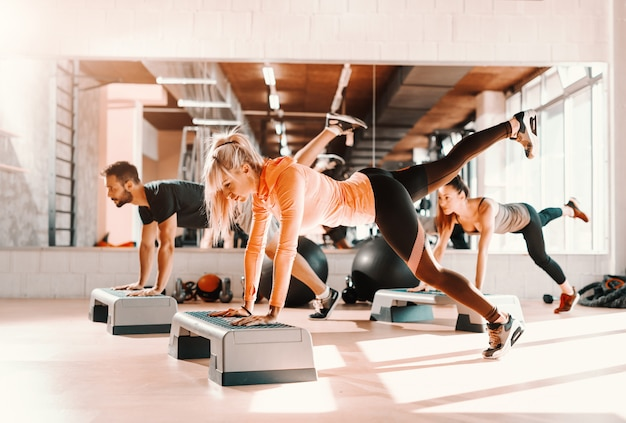 Gruppo di persone con abitudini sane facendo esercizi per le gambe su stepper. interno palestra. in fondo specchio con il loro riflesso. Foto Premium