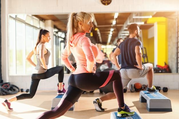 Gruppo di persone con abitudini sane facendo esercizi per le gambe su stepper. interno palestra. Foto Premium