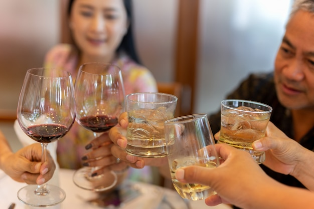 Gruppo di persone con vino rosso e wishkey facendo un brindisi al successo festa celebrazione Foto Premium
