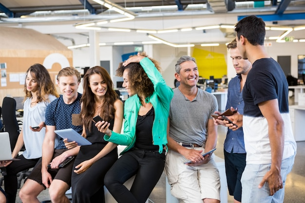 Gruppo di persone di affari che interagiscono durante il tempo di pausa in ufficio Foto Premium