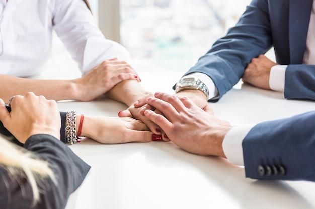 Gruppo di persone di affari che si impilano mano sullo scrittorio bianco Foto Gratuite