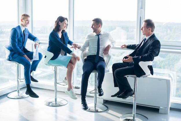 Gruppo di persone di affari che si siedono sulle feci in ufficio Foto Gratuite