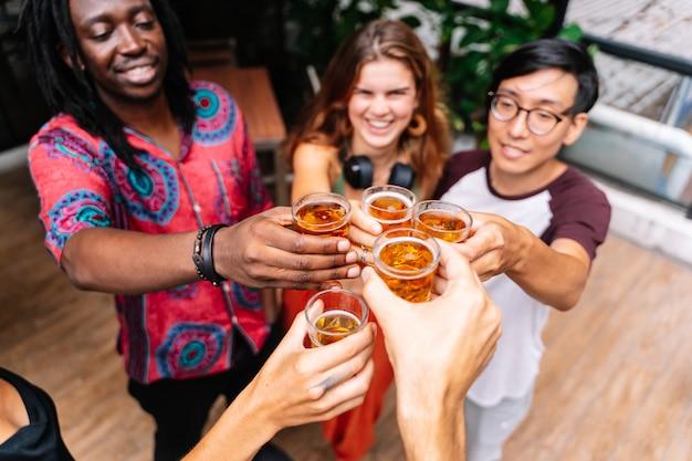 Gruppo di persone di diverse etnie che tostano con la birra Foto Premium