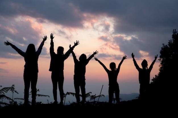 Gruppo di persone felici che giocano al tramonto estivo in natura Foto Gratuite