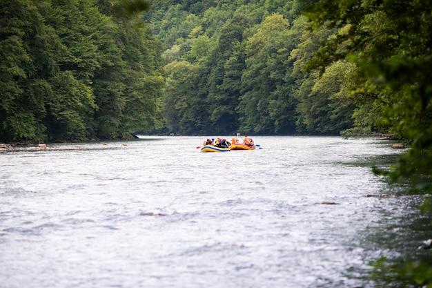 Gruppo di persone felici con guida rafting e canottaggio sul fiume. Foto Premium