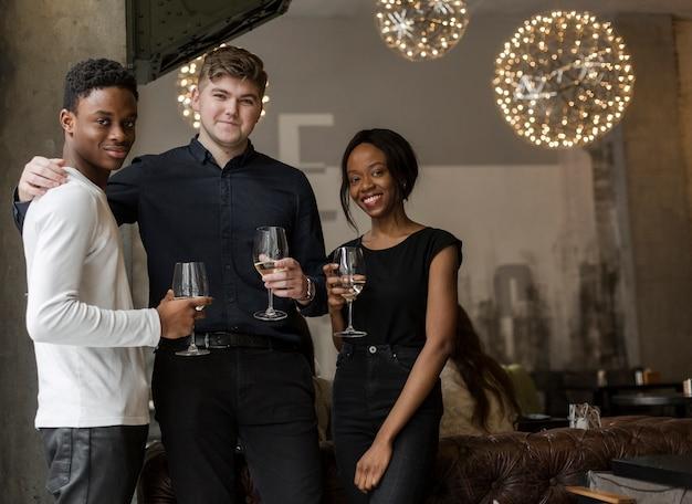 Gruppo di persone positive in posa con il vino Foto Gratuite