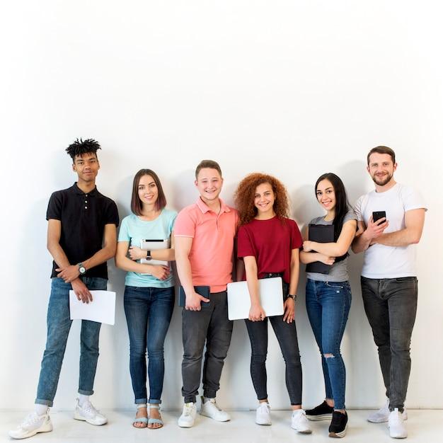 Gruppo di persone sorridente multirazziale che stanno davanti a fondo bianco che esamina macchina fotografica che tiene carta e dispositivo elettronico Foto Gratuite