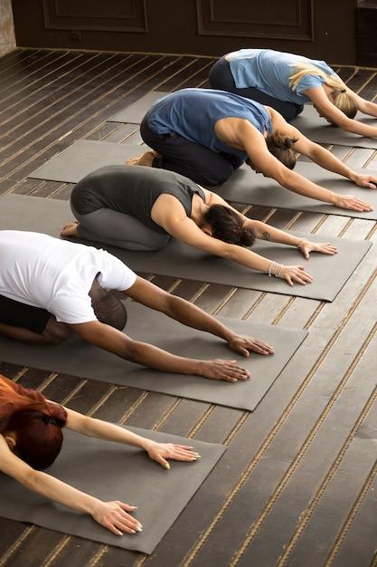 Gruppo di persone yogi in posa balasana Foto Gratuite