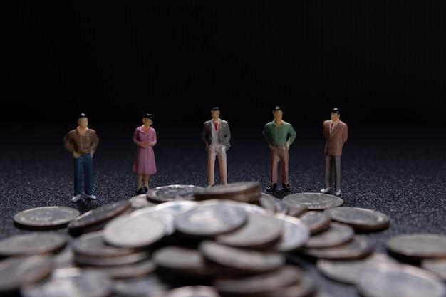 Gruppo di piccoli imprenditori in piedi sulle monete Foto Gratuite