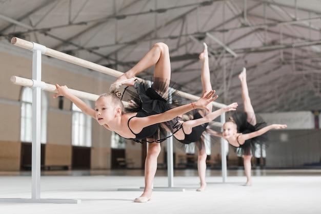 Gruppo di ragazze con la gamba in alto vicino alla sbarra durante una lezione di danza classica Foto Gratuite