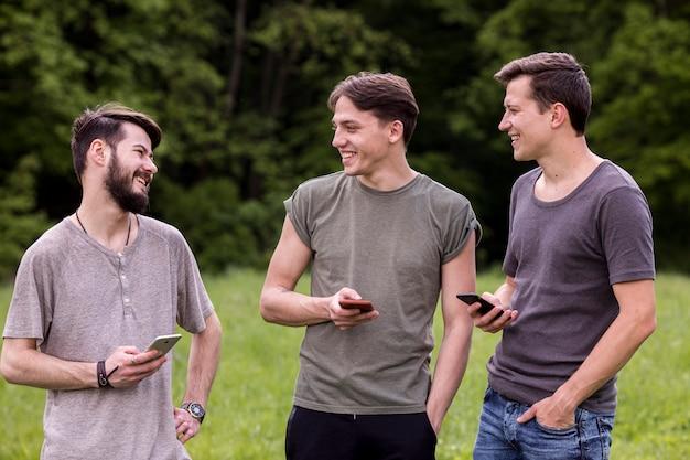 Gruppo di ragazzi felici con gli smartphone in chat in natura Foto Gratuite