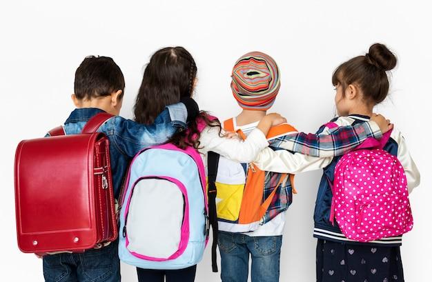 Gruppo di retrovisione di diversi bambini che indossano zaino Foto Premium