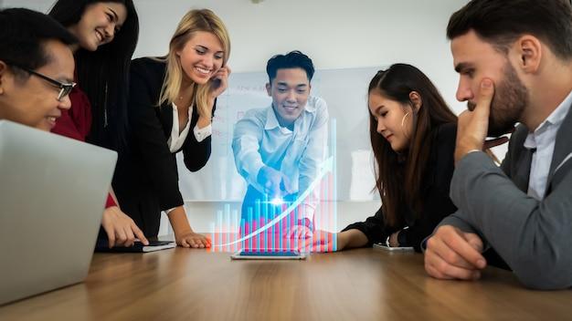 Gruppo di soci in affari riuniti presenti con ologramma grafico moderno. Foto Premium