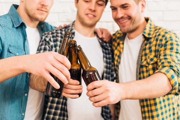 Gruppo di sorridere tre amici maschii che tintinnano la bottiglia da birra Foto Gratuite