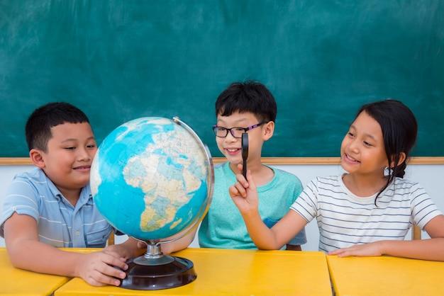 Gruppo di studenti asiatici che studiano geografia in aula Foto Premium