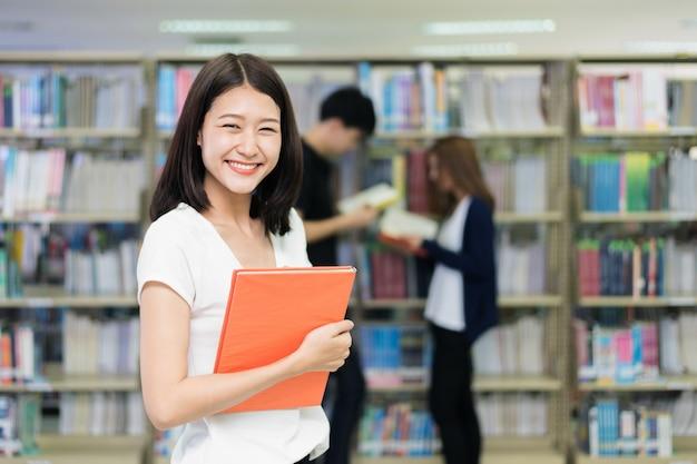 Gruppo di studenti asiatici che studiano insieme nella biblioteca all'università. Foto Premium