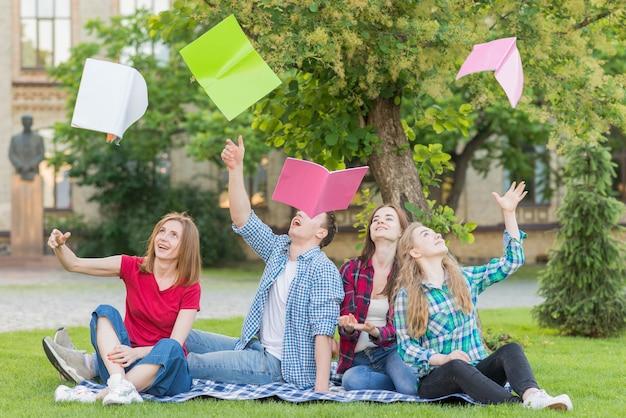 Gruppo di studenti che lanciano libri in aria Foto Gratuite