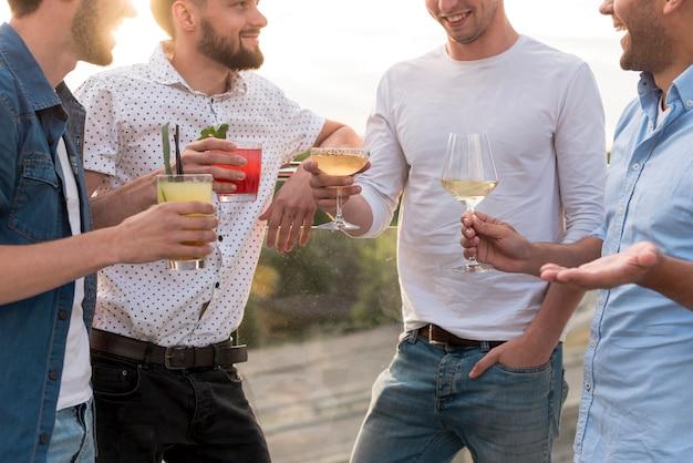 Gruppo di uomini che discutono ad una festa in terrazza Foto Gratuite
