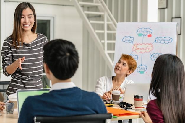 Gruppo di uomini d'affari asiatici e multietnici con tuta casual di brainstorming e di lavoro Foto Premium
