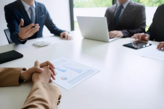 Gruppo di uomini d'affari che discutono di valutazione del bene immobile con il dirigente esecutivo in un ufficio moderno Foto Premium