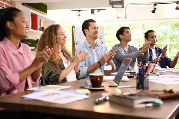 Gruppo di uomini d'affari tifo e battimani per un collega in ufficio Foto Premium