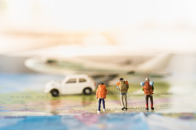 Gruppo di viaggiatori mini figure in miniatura con lo zaino che cammina sulla mappa di modello di aeroplano e auto giocattolo bianco Foto Premium