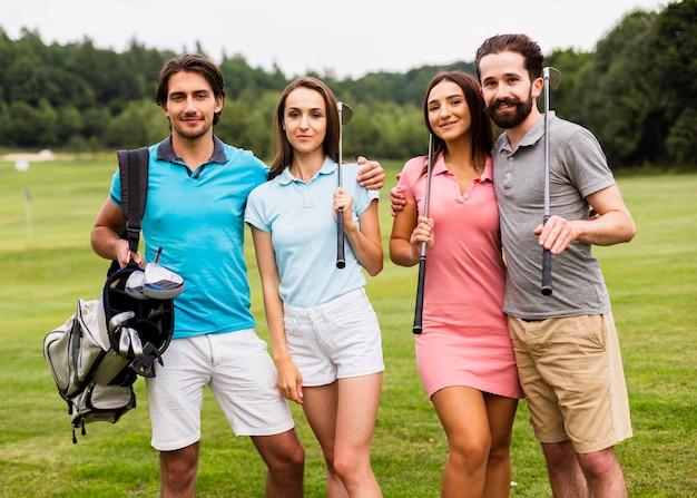 Gruppo di vista frontale di giocatori di golf che sorridono alla macchina fotografica Foto Gratuite