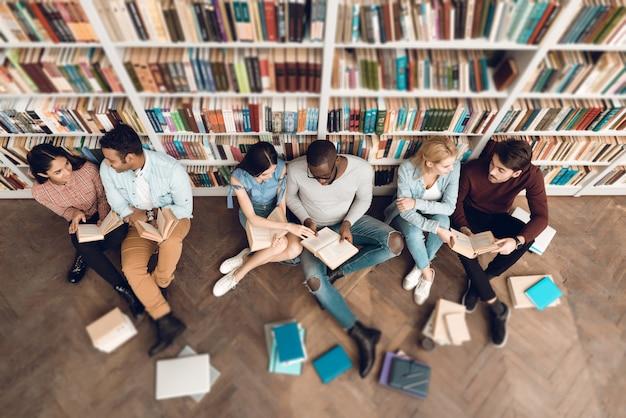 Gruppo di vista superiore di studenti multiculturali etnici in biblioteca. Foto Premium