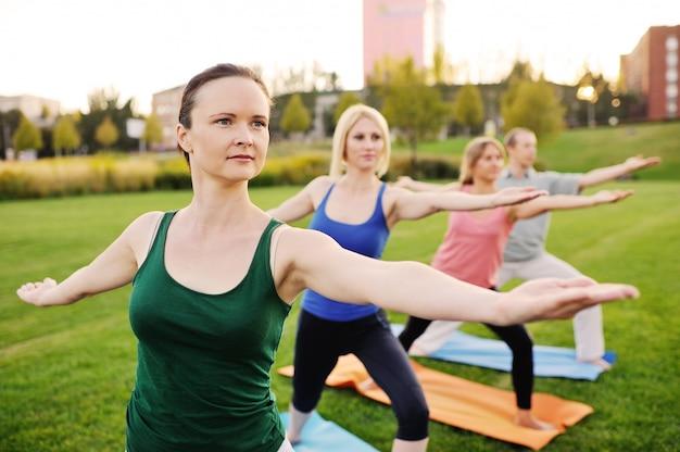 Gruppo di yoga sullo sfondo di erba verde Foto Premium