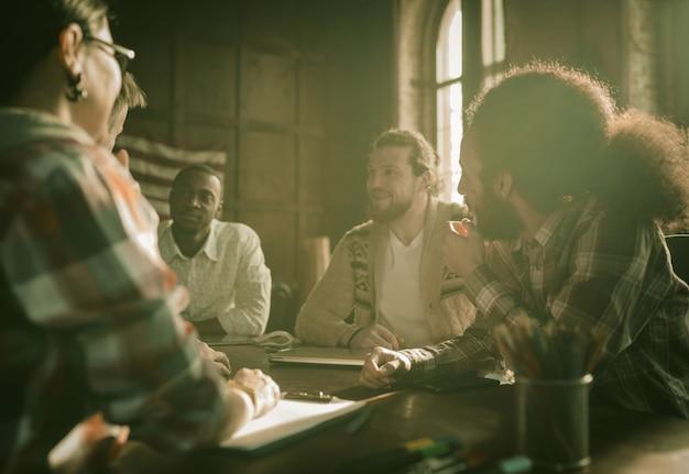 Gruppo felice di gente di affari che confronta le idee in ufficio Foto Premium