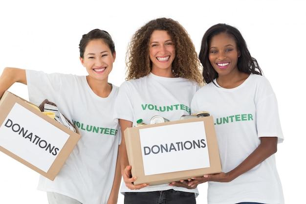Gruppo felice di volontari che sorridono alle scatole di donazioni della tenuta della macchina fotografica Foto Premium